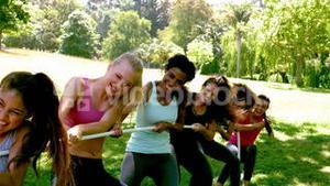 Group of fit women pulling a rope
