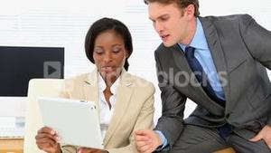 Business people talking together at desk with tablet