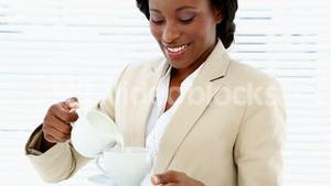 Businesswoman pouring milk into her cup