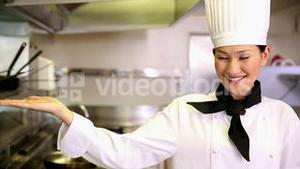 Happy chef smiling at camera holding her hand out in presentation