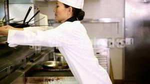 Asian chef putting away stack of plates