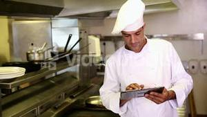 Handsome chef using tablet pc