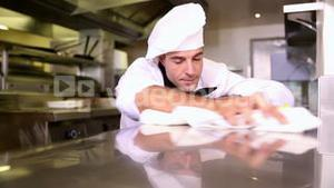 Handsome chef wiping down the counter