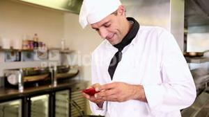 Handsome chef sending a text message