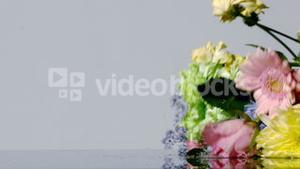 Bouquet of colourful flowers falling onto wet surface