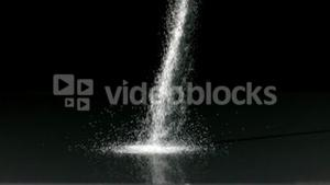 Salt pouring against black background