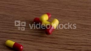 Pills falling onto wooden table