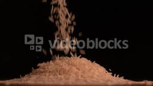 White rice pouring on black background