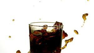 Ice cubes falling into glass of soda