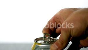 Hand opening a soda can