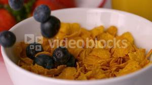 Blueberries pouring into cereal bowl at breakfast table
