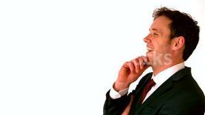 Happy businessman laughing with hand on chin