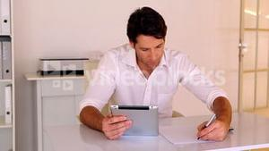 Businessman using tablet pc at his desk