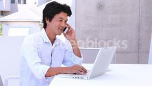 Asian man using laptop and answering his phone