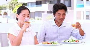 Asian couple having white wine with their meal