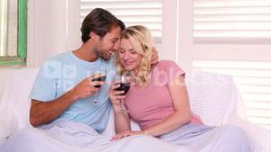 Couple sitting on sofa under blanket having red wine