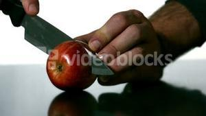 Man slicing apple with large knife