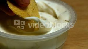 Hand dunking a chip into creamy dip