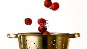 Cherry tomatoes falling into colander on white background