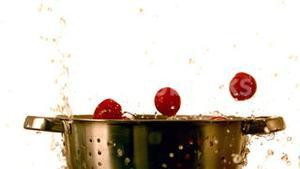 Cherry tomatoes and water falling into colander
