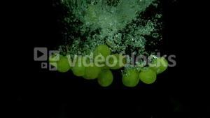 Grapes falling in water on black background