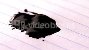 Black ink falling on lined paper