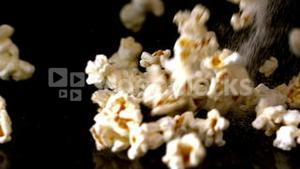 Popcorn and salt pouring onto black surface
