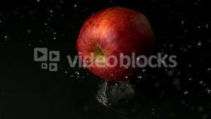Red apple falling on wet black surface