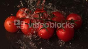 Water pouring over vine cherry tomatoes