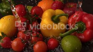 Water raining on selection of fresh fruit and vegetables