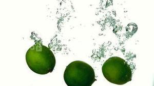 Limes plunging into water on white background