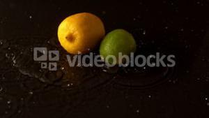 Lemon and lime dropping on wet black surface