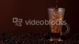 Coffee pouring into glass of ice