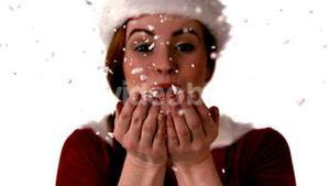 Pretty girl in santa costume blowing snow