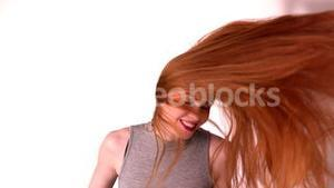 Pretty redhead tossing her long hair