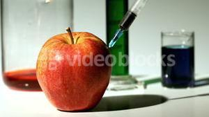 Syringe injecting chemical into an apple