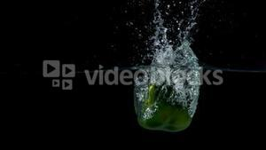 Green pepper falling in water on black background