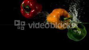 Three peppers falling in water on black background