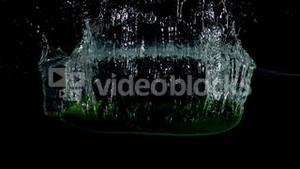 Courgette falling in water on black background