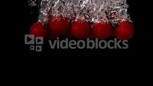Cherry tomatoes falling in water on black background