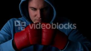 Tough boxer punching fists together with red gloves