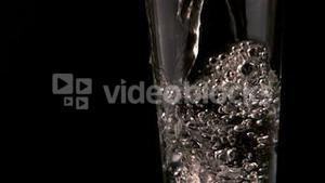 Water pouring into glass on black background