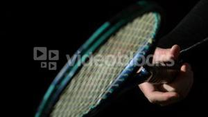 Hand spinning a tennis racket on black background