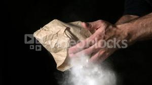 Hand popping flour bag on black background