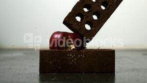 Apple being squashed between two bricks