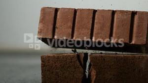 Brick falling on and breaking another