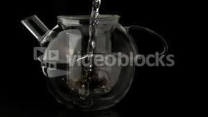 Water pouring into glass teapot over loose tea