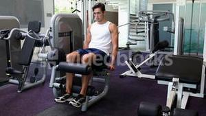 Fit man exercising his legs on weight machine