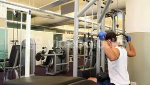 Fit man exercising his arms on weight machine