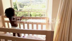 Cute baby girl standing in her crib looking out window